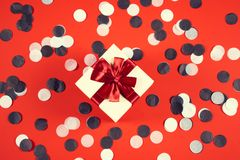 Beautiful present box on red background with confetti. stock photo