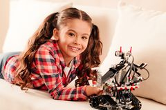 Beautiful preteen child beaming while playing with robot toy. The happiest in the world. Positive minded little girl looking into the camera with a cheerful mile Royalty Free Stock Images