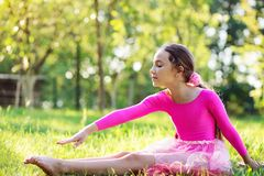 Beautiful preteen girl doing gymnastics and stretching in the ci. Cute preteen girl doing gymnastics and stretching in the city park on sunset Stock Images