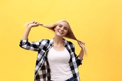 Beautiful pretty charming young blonde woman smiling happily, having fun indoors, playing with long straight hair stock photography