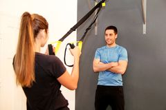 Sportswoman training with trx resistance band with trainer Stock Images