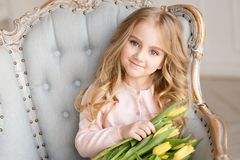 Beautiful pretty girl with yellow flowers tulips sitting in arm-chair, smiling. Indoor photo. Beautiful nice pretty girl with blue eyes and yellow flowers tulips stock image