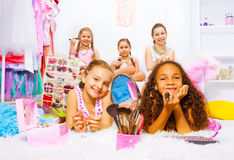 Beautiful pretty girls apply make-up on carpet. Beautiful pretty girls applying make-up laying on fluffy white carpet with friends sitting on sofa behind Royalty Free Stock Photography