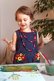 Beautiful, pretty, little girl with a smile rejoices in an incre. Dibly successful drawing and prints of her painted palms on paper Royalty Free Stock Photos