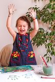 Beautiful, pretty, little girl with a smile rejoices in an incre. Dibly successful drawing and prints of her painted palms on paper Stock Image