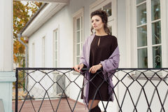 Beautiful pretty woman in a brown dress in a shawl over his shoulders came out on the veranda on a cold autumn morning Stock Photos