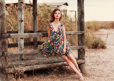 Beautiful, pretty woman in casual floral dress sitting over wood. En fence. Street fashion style Stock Photos