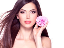 Beautiful pretty woman with long hair and pink rose at face. stock image