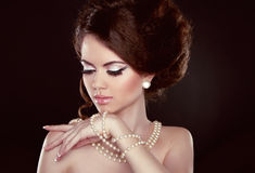 Beautiful pretty woman with pearls on her neck isolated on dark Royalty Free Stock Images