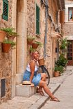 Beautiful pretty woman walking at old town pavement street with flowers and looking away. Travel concept Stock Image