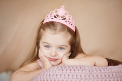 Beautiful princess girl in pink dress lying down bored. Stock Images