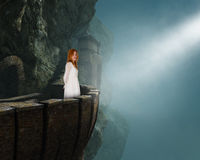 Beautiful Princess Maiden Medieval Castle. A beautiful princess wearing a white dress is standing on a stone balcony at a medieval castle. The ancient ruins are Stock Photography