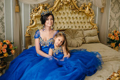 Beautiful princess mother and daughter in a gold crown Stock Photos
