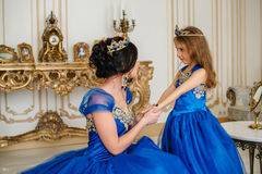 Beautiful princess mother and daughter in a gold crown Royalty Free Stock Photos