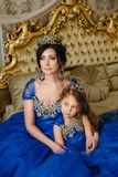 Beautiful princess mother and daughter in a gold crown Stock Photo