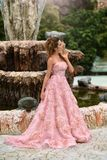 Beautiful Princess in a pink dress near the fountain. blonde woman with long hair walking through the castle.