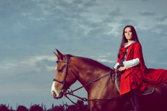 Beautiful Princess with Red Cape Riding a Horse Royalty Free Stock Photography