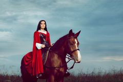 Beautiful Princess with Red Cape Riding a Horse Royalty Free Stock Photo