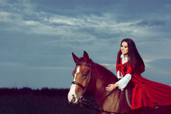 Beautiful Princess with Red Cape Riding a Horse Royalty Free Stock Photos
