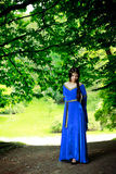 Beautiful princess in shadow of big trees Royalty Free Stock Photography