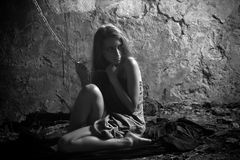 Beautiful prisoner. Black and white portrait of woman with chain in the dark cave Royalty Free Stock Photos