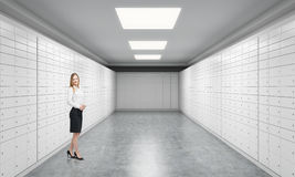 A beautiful private manger of a bank is standing in a room with safe deposit boxes. A concept of storing of important documents or Stock Photos