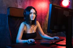 Beautiful Professional Gamer Girl Playing in First-Person Shooter Online Video Game on Her Personal Computer. Casual. Cute Geek wearing Glasses and Smiling royalty free stock photos