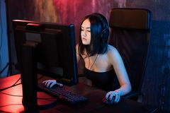 Beautiful Professional Gamer Girl Playing in First-Person Shooter Online Video Game on Her Personal Computer. Casual. Cute Geek wearing Glasses and Smiling royalty free stock image