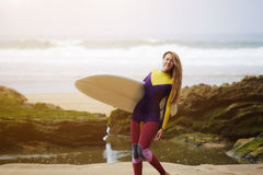 Beautiful professional  surfer with long blond hair holding surfboard Royalty Free Stock Image