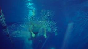 Beautiful professional swimmer doing butterfly stroke in pool, shot from underwater in slow motion. Beautiful bearded professional swimmer doing butterfly stroke stock footage