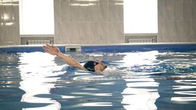 Beautiful professional swimmer swiming backstroke in the pool, camera dolly shot stock photos
