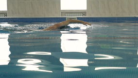 Beautiful professional swimmer swiming crawl stroke reaching the wall and doing a flip turn in the pool, camera dolly stock footage
