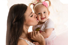 Beautiful profile face woman kissing daughter Stock Images