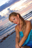 Beautiful profile portrait. Angled portrait image of beautiful blonde lady sitting on beach with waves and clouds in the background Royalty Free Stock Photos