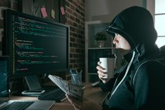 Beautiful programmer hacker drinking hot coffee. Relaxing and holding cash banknote ransom looking at computer screen supervising online virus spread stock photography
