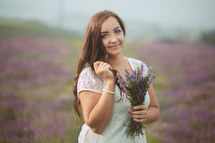 Beautiful provence woman relaxing in lavender field watching on sunset holding basket with lavanda flowers. Series. alluring girl Royalty Free Stock Photo