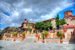 Public flower garden of monastery in Meteora, Greece. Beautiful public flowe garden of monastery in Meteora, with amazing cloud on the sky in summer holiday Stock Photo