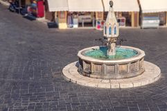 Beautiful public fountain in Rhodes town of Greek island. With marble dark block street Stock Image