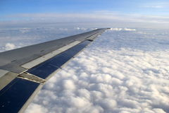 Beautiful puffy clouds and blue skies, seen from the window of a plane Royalty Free Stock Photo