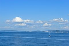 Beautiful Puget Sound. Sailboat motoring on Puget Sound on a sunny summer day Stock Images