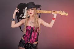 Beautiful punk girl with lots of tattoos posing with guitar Stock Photography