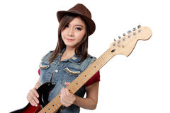 Beautiful punk rock girl with her guitar, on white background. Beautiful Asian punk rocker girl in jeans jacket and fedora hat posing with her electric guitar Royalty Free Stock Image