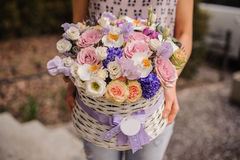 Beautiful purple  bouquet of mixed flowers in basket hold by woman Royalty Free Stock Photos