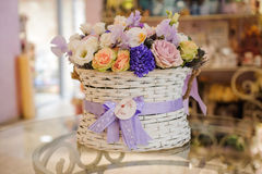 Beautiful purple  bouquet of mixed flowers in basket on table Stock Photography