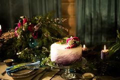 Beautiful purple cake with streaks of white cream and decorated with berries BlackBerry, blueberry and cherry. Over blue wooden ta Stock Photo