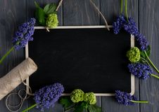 Beautiful purple and green flowers with a blackboard for writing on a gray wooden background. Frame for greeting banner, greeting royalty free stock images