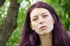Beautiful purple haired girl looking serious on a green background. Beautiful purple haired girl looking serious on a green leafed background with selective stock photos