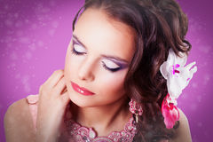 Beautiful purple makeup on the girl with closed eyes on purple. Portrait of curly brunette with closed eyes. Lady with purple make-up in pink dress with pink stock photo