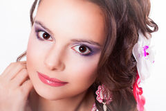 Beautiful purple makeup on the girl with pink lips. Portrait of curly brunette with purple make-up with pink soutache technique decorations with flowers in her royalty free stock photography