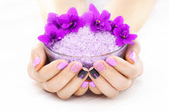 Beautiful purple manicure with violet, candle and sea salt on the white wooden table. Royalty Free Stock Photography